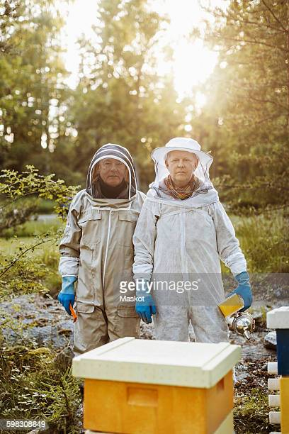 Portrait of confident beekeepers standing on field