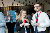 Portrait of confident business people holding coffee cups at lobby in convention center