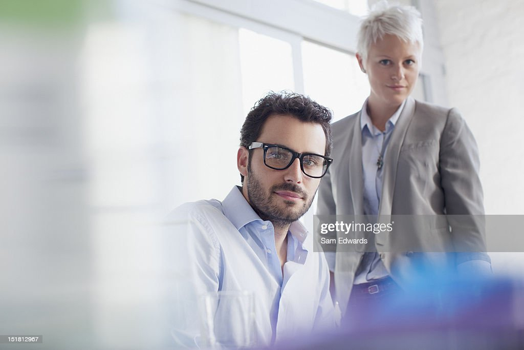 Portrait of confident businessman and businesswoman in office : Stock Photo