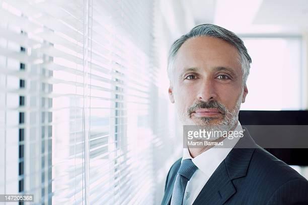 Portrait of confident businessman at window