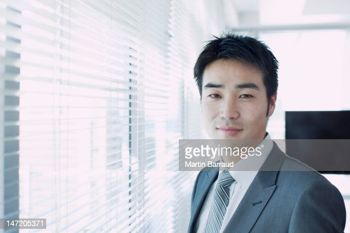 Portrait of confident businessman at window : Stock Photo