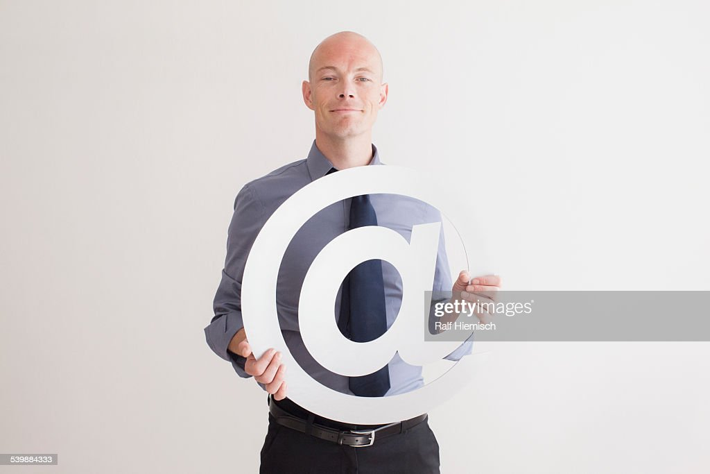 Portrait of confident businessman holding at symbol against white background