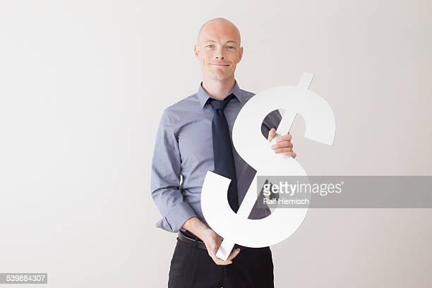 Portrait of confident businessman holding dollar sign against white background