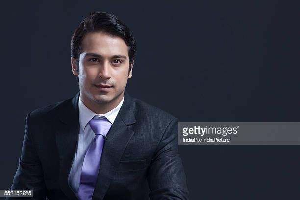 Portrait of confident businessman over black background