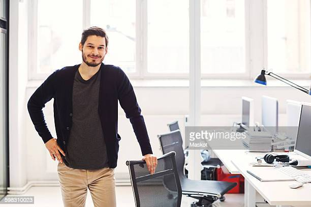 Portrait of confident businessman standing by desk in office