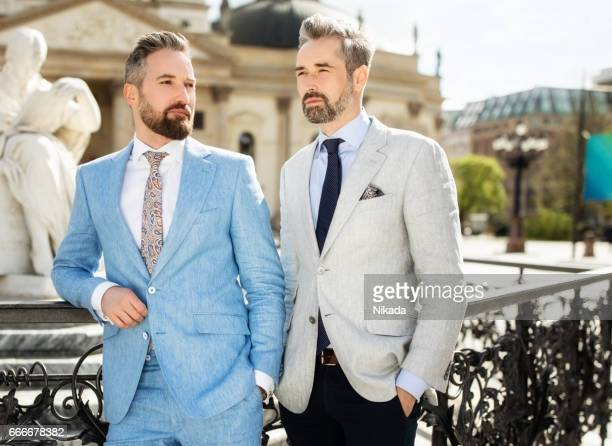 Portrait of confident businessman standing with friend at town square in city