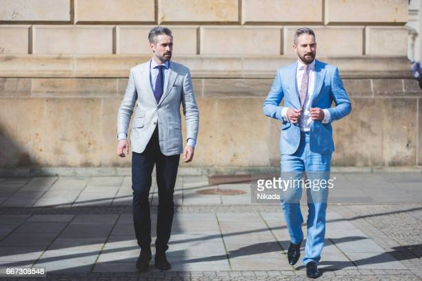 Portrait of confident businessman walking with friend at town square in city