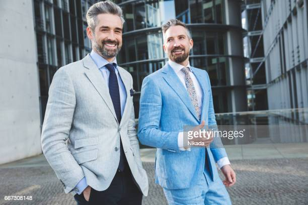 Portrait of confident businessman walking with friend