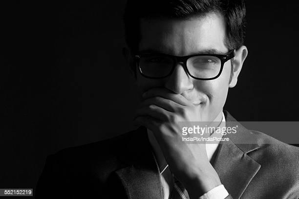 Portrait of confident businessman wearing glasses against black background
