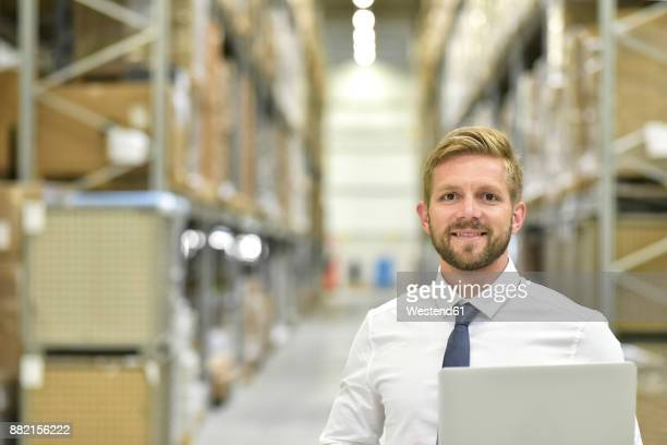 Portrait of confident businessman with laptop in warehouse