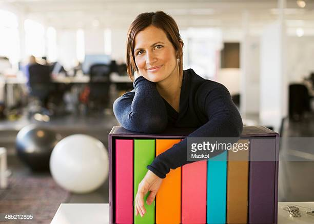 Portrait of confident businesswoman leaning on folder rack in office