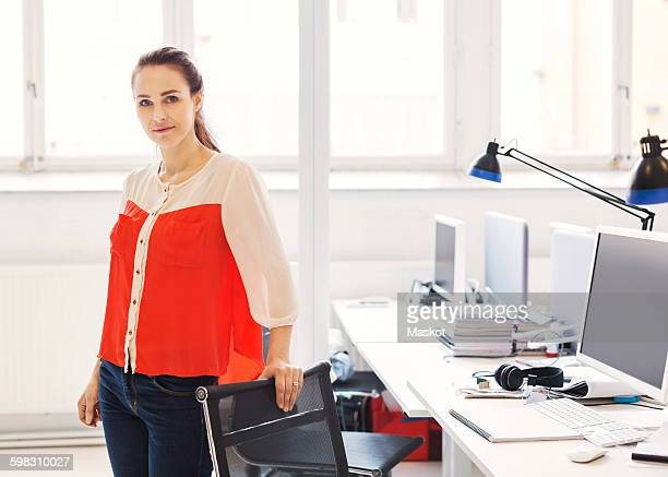 Portrait of confident businesswoman standing by desk in office