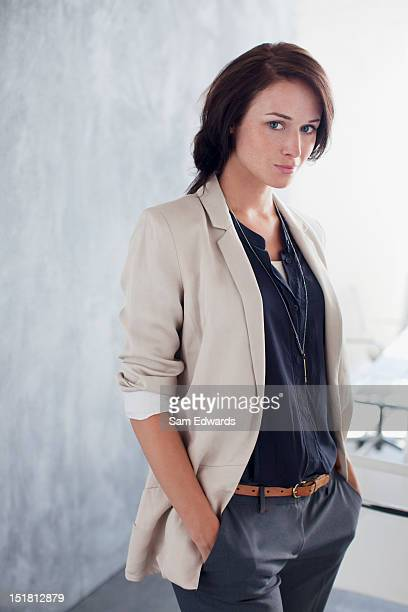 Portrait of confident businesswoman with hands in pockets in office