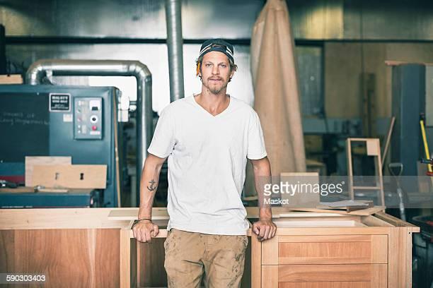 Portrait of confident carpenter leaning on cabinet in workshop