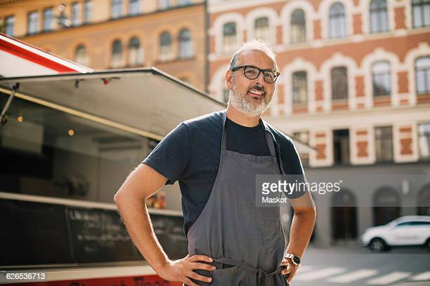 Portrait of confident chef standing by food truck on street in city