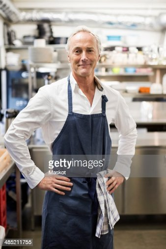 Portrait of confident chef standing in commercial kitchen