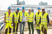 Portrait of confident construction team standing together at site