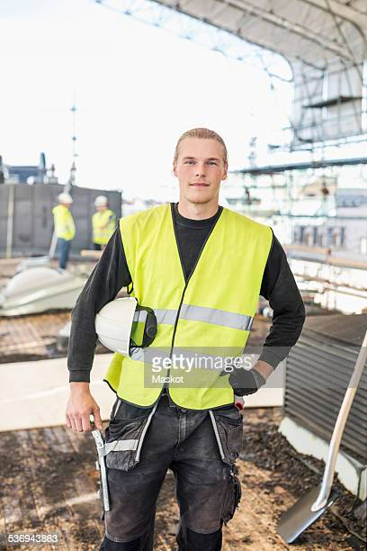 Portrait of confident construction worker standing at site