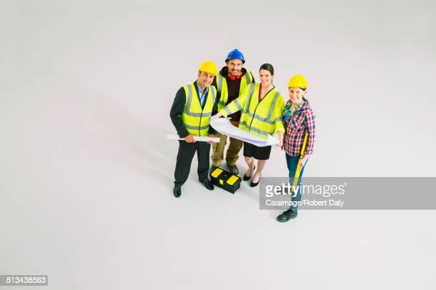 Portrait of confident construction workers with blueprints