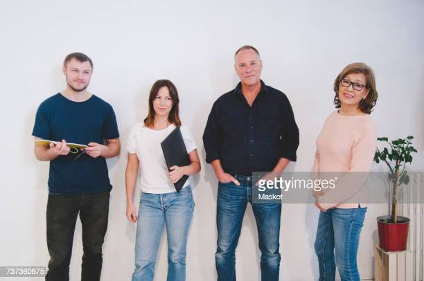 Portrait of confident creative business people standing against white wall in office