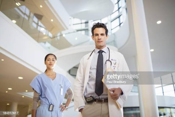 Portrait of confident doctor and nurse in hospital atrium