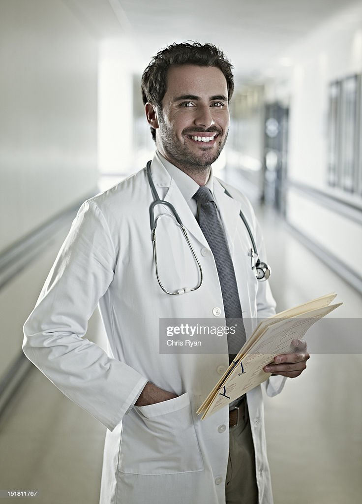 Portrait of confident doctor holding medical record in hospital corridor : Stock Photo
