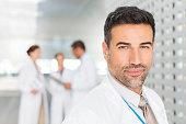 Portrait of confident doctor in hospital corridor