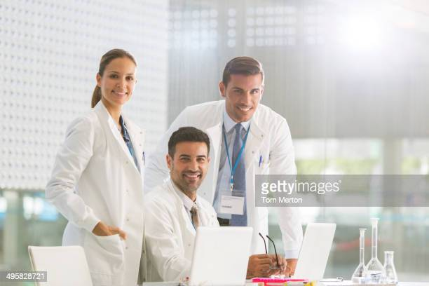 Portrait of confident doctors working at laptop