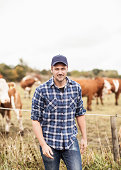 Portrait of confident farmer standing on field while animals grazing in background