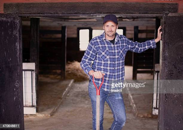 Portrait of confident farmer with pitchfork standing at the entrance of barn