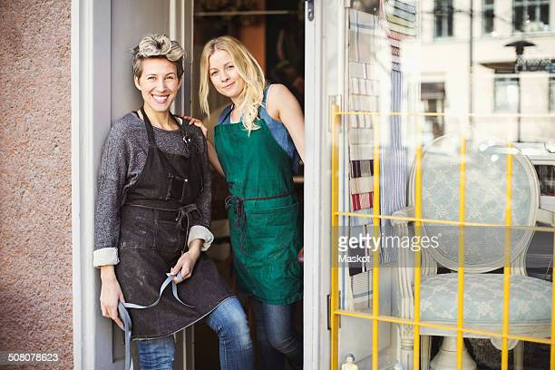 Portrait of confident fashion designers at studio doorway