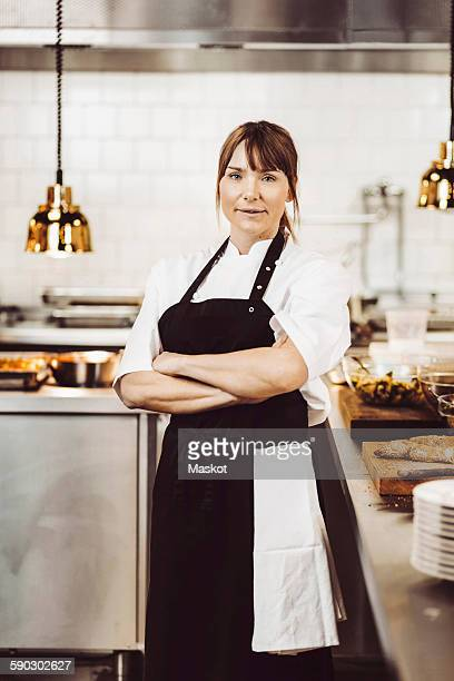 Portrait of confident female chef standing arms crossed in commercial kitchen