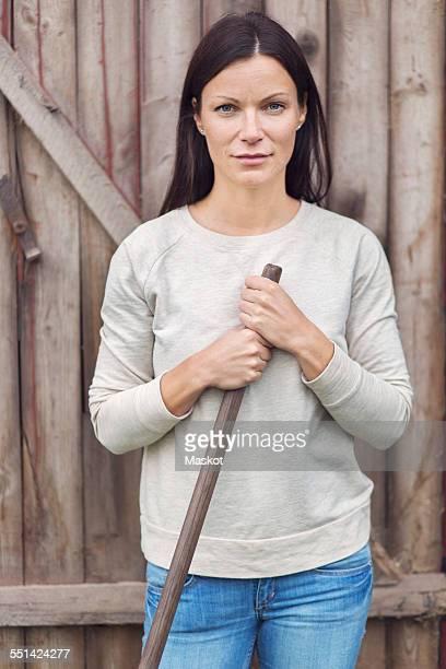 Portrait of confident female farmer standing against wooden door