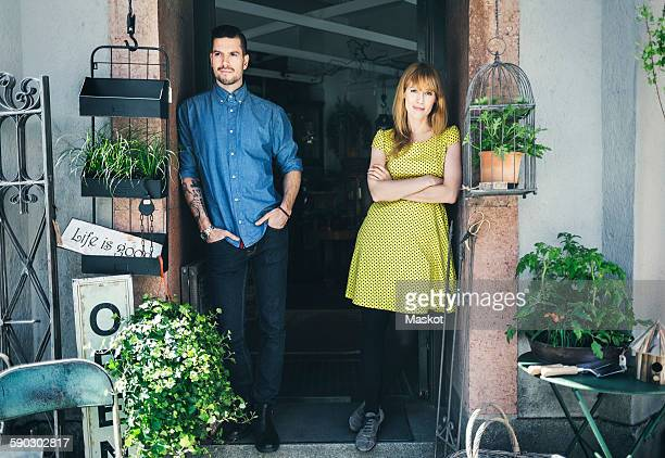 Portrait of confident female owner with colleague leaning at store doorway
