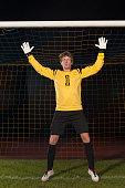 Portrait of confident goalie defending soccer net on field