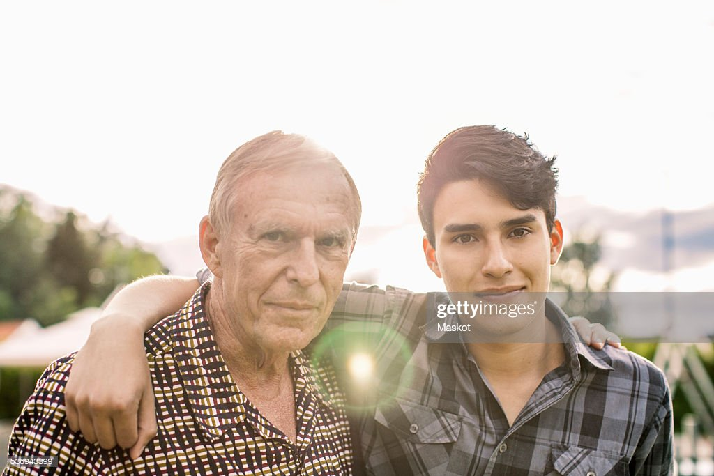 Portrait of confident grandfather and grandson with arms around against sky