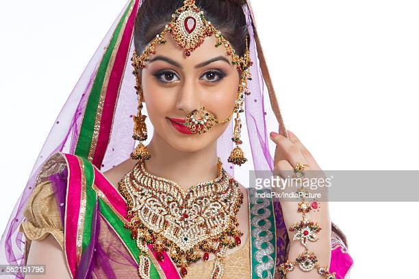 Portrait of confident Indian bride over white background
