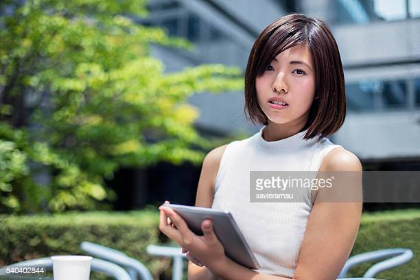 Portrait of confident Japanese businesswoman with digital tablet