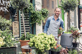 Portrait of confident male florist working outside flower shop