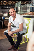 Portrait of confident male owner sitting on chair in bakery