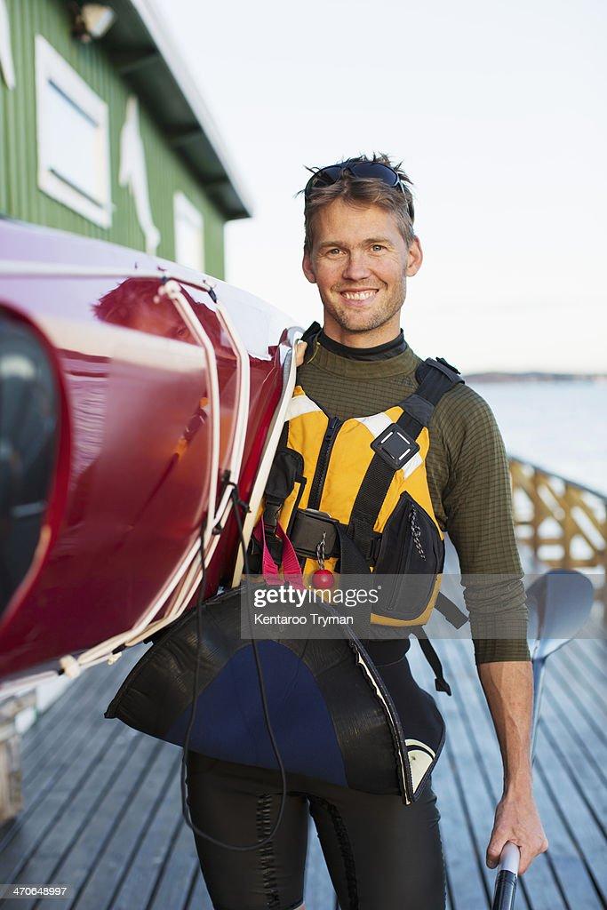 Portrait of confident man carrying kayak on shoulder at boathouse