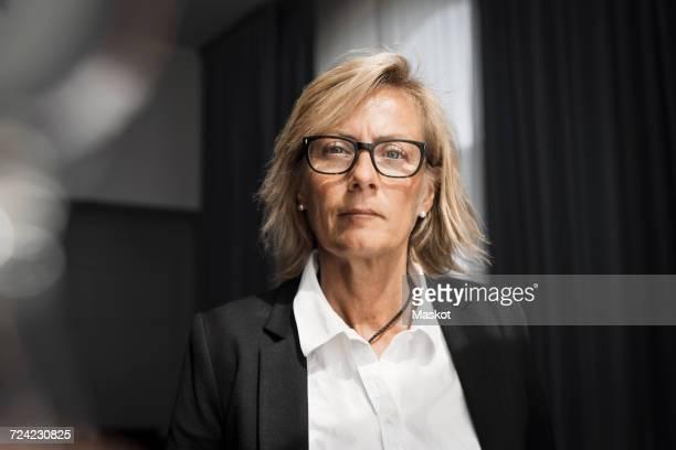 Portrait of confident mature businesswoman in hotel room