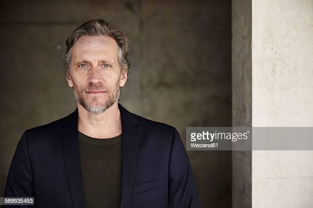 Portrait of confident mature man at concrete wall