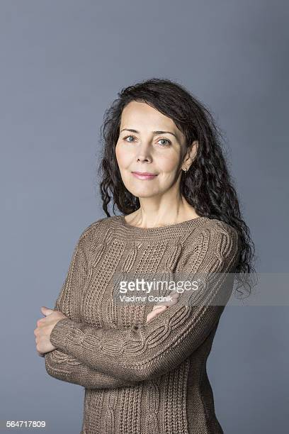 Portrait of confident mature woman standing arms crossed over gray background