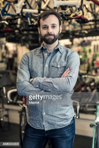 Portrait of confident mid adult male owner standing arms crossed at bicycle repair shop : Stock Photo