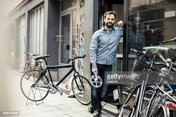 Portrait of confident mid adult male owner with pedal standing at the entrance of bicycle repair shop