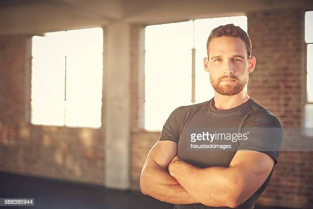 Portrait of confident muscular man standing arms crossed in gym
