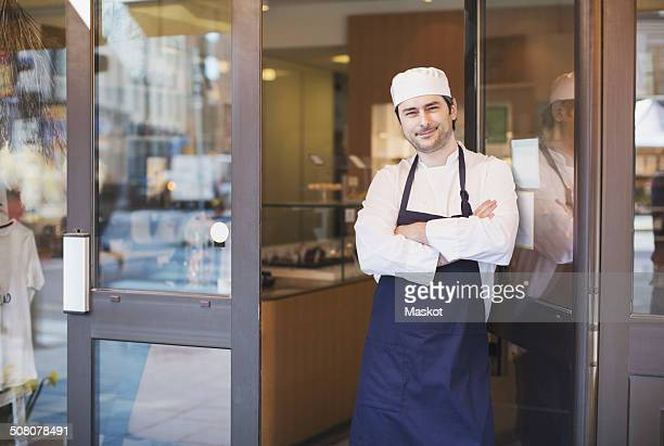 Portrait of confident owner standing with arms crossed at cafe entrance