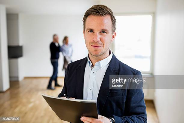 Portrait of confident real estate agent with couple standing in background at home