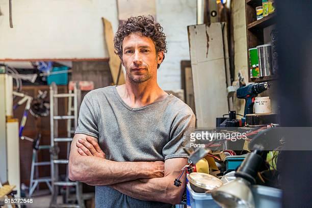Portrait of confident repairman in workshop